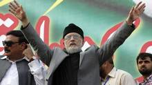 Tahir ul Qadri, Sufi cleric and leader of political party Pakistan Awami Tehreek, gestures to supporters during a demonstration outside his residence in Lahore on Aug. 10, 2014. (MOHSIN RAZA/REUTERS)
