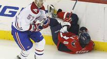 Montreal Canadiens' Benoit Pouliot (L) sends Washington Capitals' Alex Ovechkin crashing into the boards during the first period of action in Game 7 of their NHL Eastern Conference quarter-final hockey series in Washington, April 28, 2010. (JIM YOUNG/REUTERS)