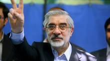 Former Iranian prime minister and presidential candidate Mir Hossein Mousavi flashes the V sign after casting his vote at a polling station at the Ershad mosque on Friday in Tehran, Iran. (Majid/2009 Getty Images)