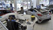 Sales staff work on deals with customer inside Hyundai of Mississauga. (J.P. MOCZULSKI FOR THE GLOBE AND MAIL)
