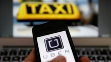 The logo of car-sharing service app Uber on a smartphone next to the picture of a taxi sign. (© Kai Pfaffenbach / Reuters)