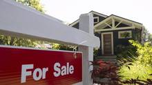 FILE - Home sales in the Vancouver area tumbled 26 per cent in August compared to the same month last year, as observers say a new tax on foreign buyers accelerated a cooling trend in the market. A for sale sign is pictured outside a home in Vancouver in a June, 28, 2016, file photo. THE CANADIAN PRESS/Jonathan Hayward, File