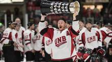 University of New Brunswick Varsity Reds' Cam Braes holds the University Cup after beating the University of Saskatchewan Huskies on March 19, 2017. (Stephen MacGillivray/The Canadian Press)