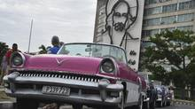 A vintage car is parked in front of a building with an image of former Cuban President Fidel Castro at Havana's Revolution square on March 19, 2016. (YURI CORTEZ/AFP/Getty Images)
