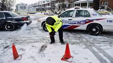 A police officer lights a flare on the scene after they stopped a stolen snowplow involved in the death of a police officer on Jan. 12, 2010. (Nathan Denette)
