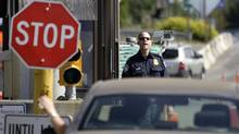 A U.S. Customs and Border Protection officer looks toward a car coming toward at the border crossing between the U.S. and Canada, in Blaine, Wash. (Elaine Thompson)