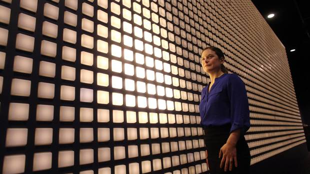 Historian Melanie Morin-Pelletier stands next to an interactive display at the Canadian War Museum. Each light commemorates one of the 3,598 Canadian soldiers killed at the Battle of Vimy Ridge.