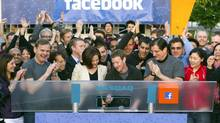 Mark Zuckerberg, chief executive officer of Facebook Inc., center, Sheryl Sandberg, chief operating officer of Facebook, center left, and Robert Greifeld, chief executive officer of Nasdaq OMX Group Inc., center right, remotely ring the opening bell for trading at the Nasdaq MarketSite from the Facebook campus in Menlo Park, Calif., on May 18, 2012. (Zef Nikolla/Bloomberg News)