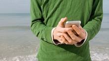 Text messaging at the beach (PhotoAlto/Michele Constantini/Getty Images/PhotoAlto)