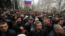 Pro-Russian protesters wave Russia's flag gathered in front of city hall in the Ukrainian Black Sea port of Sevastopol in the Crimea Feb. 24, 2014. (Darko Vojinovic/Associated Press)