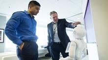 ATB Financial CEO Dave Mowat, right, and University of Alberta student Nabaa Alam talk to a robot named Pepper at the ATB Campus in Calgary on Tuesday. (Todd Korol/The Globe and Mail)