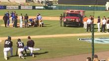 In this photo provided by Nick Brzezinski, players and staff watch as Toronto Blue Jays reliever T.J. House is tended to by emergency personnel after he was struck in the head by a line drive during a spring training baseball game against the Detroit Tigers, Friday, March 10, 2017, in Lakeland, Fla. House was talking before the ambulance left the field, Toronto manager John Gibbons said. (Nick Brzezinski/AP)