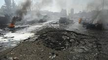 Vehicles burn near a crater on a road after an explosion at central Damascus February 21, 2013, in this handout photograph. (SANA/REUTERS)
