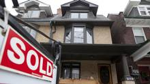A house with a sold sign is seen in Toronto in this file photo. (Matthew Sherwood For The Globe and Mail)