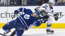 Toronto Maple Leafs' Richard Panik, left, battles for the puck with Minnesota Wild's Jordan Leopold during second period NHL hockey action in Toronto on Monday, March 23, 2015. (Chris Young/THE CANADIAN PRESS)
