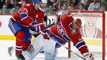 Hal Gill picks up the loose puck to the side of teammate Jaroslav Halak of the Montreal Canadiens in Game Six of the Eastern Conference Quarterfinals against the Washington Capitals during the 2010 NHL Stanley Cup Playoffs at the Bell Centre on April 26, 2010 in Montreal, Quebec, Canada. (Richard Wolowicz/Getty Images)