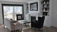 Furniture placement came naturally, with our tufted sofa facing the fireplace and two glam black wing chairs from Structube on either side.