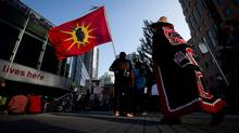 oe Taylor, left, of Curve Lake, Ont., who is half Mohawk and half Ojibwa, holds a Mohawk flag during a rally held to show opposition to the Enbridge Northern Gateway pipeline in Vancouver, B.C., on Tuesday June 17, 2014. (DARRYL DYCK/THE CANADIAN PRESS)