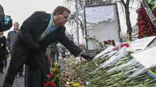 Canadian Foreign Affairs Minister John Baird lays flowers at a makeshift memorial for those killed in recent violence in Kiev on Feb. 28, 2014. (VALENTYN OGIRENKO/REUTERS)