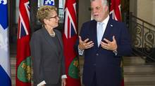 Ontario Premier Kathleen Wynne listens to Quebec Premier Philippe Couillard at the Premier's office in Quebec City on Aug. 21, 2014. (CLÉMENT ALLARD/THE CANADIAN PRESS)
