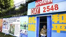 A women sits in the Falun Gong protest shed at the Chinese Consulate on August 11, 2008 in Vancouver. (Jennifer Roberts/The Globe and Mail/Jennifer Roberts/The Globe and Mail)