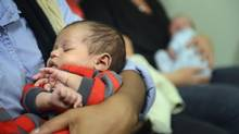 Lius-Mario Carrington-Rodriguez, four weeks old, is held by his mother during a press conference about pay equity for midwives in Toronto on Nov. 27, 2013. (FRED LUM/THE GLOBE AND MAIL)
