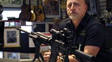 Pawn shop owner Frank James is seen on Dec. 18, 2012, after deciding to discontinue the selling of all firearms, including a Bushmaster AR15, pictured, at his shop Loanstar Jewelry and Pawn in Seminole, Fla. James said he made his decision after the mass shooting in Newtown, Conn. He is the father of a six-year-old girl, who is in the first grade. (Dirk Shadd/The Tampa Bay Times/AP)