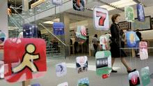 A woman walks past icons for Apple applications at the company's retail store in San Francisco, California (ROBERT GALBRAITH)