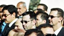 In this June 13, 2000, file photo, Syrian President Bashar al-Assad, right, his brother Maher, middle, and brother-in-law Major-General Assef Shawkat, left, stand during the funeral of late president Hafez Assad in Damascus. (STR/Associated Press)