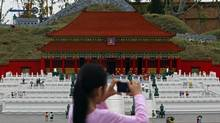 A child takes pictures of models of China's Forbidden City and the Great Wall of China during a media preview of Legoland Malaysia at Nusajaya in the southern state of Johor Sept. 14, 2012. (Edgar Su/Reuters)