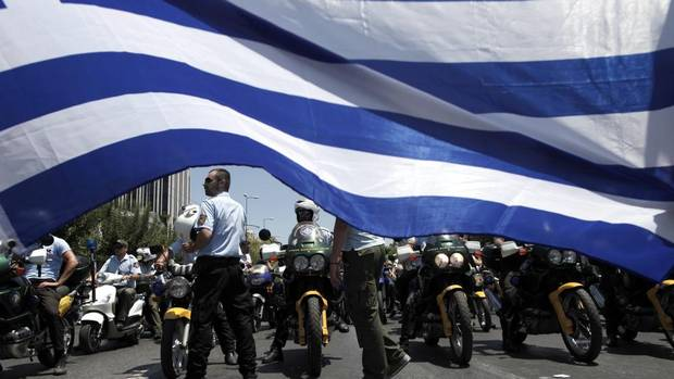 Greek Municipal police officers on motorbikes protest in front of a Greek flag in central Athens on Monday. On Sunday, the Greek government was given more time to make staff cuts. About 25,000 state workers must be moved into a so-called 'mobility scheme' by the end of 2013, meaning they will be transferred or laid off within a year. (PETROS GIANNAKOURIS/AP)