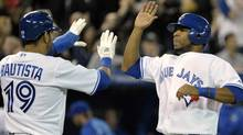 Toronto Blue Jays base runners Jose Bautista and Edwin Encarnacion (R) celebrate after scoring runs against the Seattle Mariners during the eighth inning of their MLB American League baseball game in Toronto April 29, 2012. REUTERS/Mike Cassese (MIKE CASSESE)