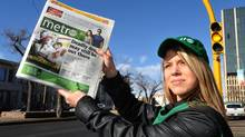 A promoter holds up a copy of the METRO newspaper in downtown Regina which began free daily distribution in Regina in 2012 (ROY ANTAL For The Globe and Mail)