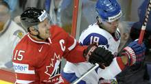 Canada's Ryan Getzlaf, left, tackles Slovakia's Tomas Starosta during match Canada vs Slovakia of 2012 IIHF Ice Hockey World Championships in Helsinki on Friday. (Martti Kainulainen/Associated Press)