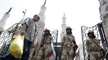 Egyptian Army soldiers stand guard Thursday outside the Rabaah al-Adawiya mosque, in the center of the largest protest camp of supporters of ousted president Mohammed Morsi, that was cleared by security forces, in the district of Nasr City, Cairo. (Hassan Ammar/Associated Press)