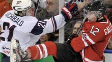 Canada forward Brendan Gallagher (12) and United States forward Josh Archibald (21) go into the boards during first period IIHF World Junior Championships hockey action in Edmonton on Saturday, Dec. 31, 2011. THE CANADIAN PRESS/Nathan Denette (Nathan Denette/CP)