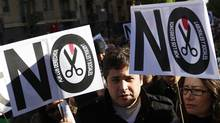 Protesters hold signs during a demonstration to protest cuts in health reforms in Madrid, April 15, 2012. (Andrea Comas/Reuters/Andrea Comas/Reuters)