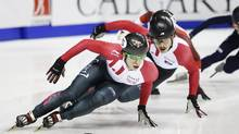 Canada's Charle Cournoyer, left, skates to a gold medal as teammate Samuel Girard, right, skates to a silver medal in the men's 1,000-metre short-track speed skating final in Calgary on Nov. 6, 2016. (Jeff McIntosh/The Canadian Press)