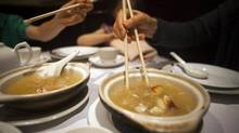 A family eats shark fin soup at Vancouver's Grand Honor Chinese restaurant in Vancouver, British Columbia July 1, 2012. Animal rights advocates criticise the shark fin harvest but others say that eating shark fins is an old cultural tradition. (BEN NELMS/REUTERS)
