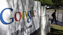 In this June 5, 2014 photo, a man walks past a Google sign at the company's headquarters in Mountain View, Calif. (Marcio Jose Sanchez/AP)