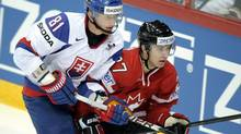 Slovakia's Marcel Hossa (L) and Canada's Ryan Murray fight for the puck during match Canada vs Slovakia of 2012 IIHF World Championships in Helsinki on Friday, 4 May, 2012. (Martti Kainulainen/AP)