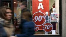 People walk past a shop with a sale advertisement in St. Petersburg November 7, 2014. (ALEXANDER DEMIANCHUK/REUTERS)