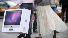 A couple carries a new Mac desktop just bought from the Apple store in Beijing on May 8, 2011. (LIU JIN/AFP/Getty Images)