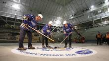 Peter Gilgan, founder and CEO of Mattamy Homes, left, faces off against Sheldon Levy, president and vice-chancellor of Ryerson University during a ceremonial puck drop by John Carmichael, MP for Don Valley West, inside the old Maple Leaf Gardens on Nov. 29, 2011. (Peter Power/The Globe and Mail/Peter Power/The Globe and Mail)