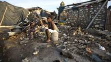 A woman and a child sit amid the ruins of their home destroyed by Hurricane Matthew, in Jeremie, Haiti, Monday, Oct. 10, 2016. Almost a week after Matthew's assault, power is still out and water and food are scarce. (Dieu Nalio Chery/AP)