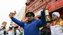 Valentin Davydyants, captain of Russia's flagship northern icebreaker, hoists the Olympic Flame before heading to the North Pole. (Fedoseyev Lev/ITAR-TASS/Newscom)