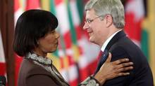 Prime Minister Stephen Harper is embraced by Jamaican Prime Minister Portia Simpson after holding a joint news conference on Parliament Hill in Ottawa Monday, October 22, 2012. (FRED CHARTRAND/THE CANADIAN PRESS)
