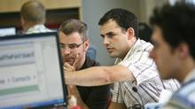 GrantStream software developers, from centre left, Josh Davis and Andrew Miles trouble shoot a design issue on one of their company's software templates. (Glenn Lowson/Glenn Lowson for The Globe and Mail)