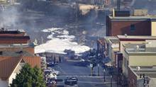 Charred vehicles and fire retardant foam can be seen in front of the destroyed Musi-Café on the main road in downtown Lac-Mégantic, Que., July 7, 2013. A train carrying crude oil tankers derailed early Saturday and burst into flames. (Moe Doiron/The Globe and Mail)