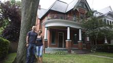 Tim Hughes and Rozita Razavi pose for a photograph in front of their recently purchased Parkdale home in Toronto, on August 22, 2014. (Matthew Sherwood for The Globe and Mail)